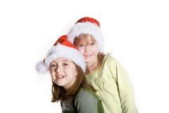 Celebrate. 2 sisters wearing santa hats Royalty Free Stock Photo