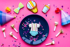 Celebrate birthday of a little baby. Cookies in shape of accesssories for child, confetti on pink background top view.  stock photo
