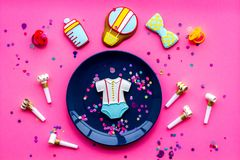 Celebrate birthday of a little baby. Cookies in shape of accesssories for child, confetti on pink background top view.  royalty free stock photography