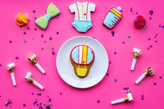 Celebrate birthday of a little baby. Cookies in shape of accesssories for child, confetti on pink background top view.  royalty free stock photos