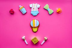 Celebrate birthday of a little baby. Cookies in shape of accesssories for child and gift box on pink background top view.  stock photos