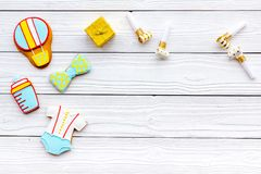 Celebrate birthday of a little baby. Cookies in shape of accesssories for child and gift box on white wooden background. Top view royalty free stock images
