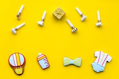 Celebrate birthday of a little baby. Cookies in shape of accesssories for child and gift box on yellow background top. View stock image