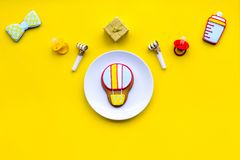 Celebrate birthday of a little baby. Cookies in shape of accesssories for child and gift box on yellow background top. View royalty free stock photography