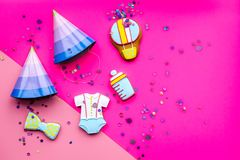 Celebrate birthday of a little baby. Cookies in shape of accesssories for child and party hats on pink background top. View royalty free stock image