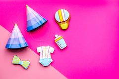 Celebrate birthday of a little baby. Cookies in shape of accesssories for child and party hats on pink background top. View stock photography