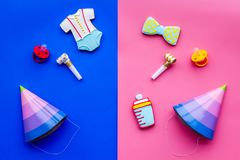 Celebrate birthday of a little baby. Cookies in shape of accesssories for child and party hats on pink and blue. Background top view royalty free stock photos