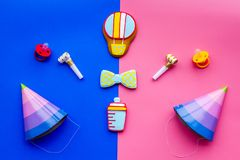 Celebrate birthday of a little baby. Cookies in shape of accesssories for child and party hats on pink and blue. Background top view stock photography