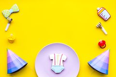Celebrate birthday of a little baby. Cookies in shape of accesssories for child and party hats on yellow background top. View royalty free stock photo
