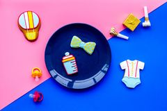 Celebrate birthday of a little baby. Cookies in shape of accesssories for child on pink and blue background top view.  stock photo