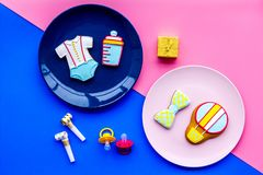 Celebrate birthday of a little baby. Cookies in shape of accesssories for child on pink and blue background top view.  stock photos