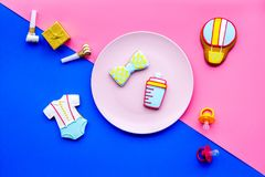 Celebrate birthday of a little baby. Cookies in shape of accesssories for child on pink and blue background top view.  royalty free stock photos