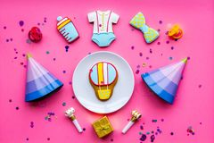 Celebrate child`s birthday. Cookies in shape of baby accesssories, party hats, gift box, confetti on pink background top. View royalty free stock photo
