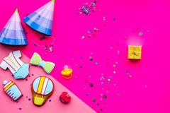 Celebrate child`s birthday. Cookies in shape of baby accesssories, party hats, gift box, confetti on pink background top. View royalty free stock photography