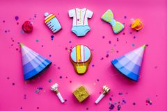Celebrate child`s birthday. Cookies in shape of baby accesssories, party hats, gift box, confetti on pink background top. View stock images