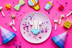 Celebrate child`s birthday. Cookies in shape of baby accesssories, party hats, gift box, confetti on pink background top. View stock image