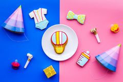 Celebrate child`s birthday. Cookies in shape of baby accesssories, party hats, gift box, confetti on pink and blue. Celebrate child`s birthday. Cookies in shape stock photography
