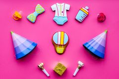 Celebrate child`s birthday. Cookies in shape of baby accesssories, party hats, gift box on pink background top view.  stock photos