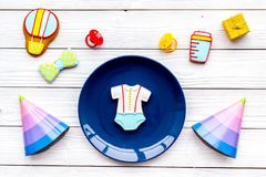 Celebrate child`s birthday. Cookies in shape of baby accesssories, party hats, gift box on white wooden background top. View stock images