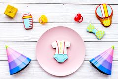 Celebrate child`s birthday. Cookies in shape of baby accesssories, party hats, gift box on white wooden background top. View stock photo