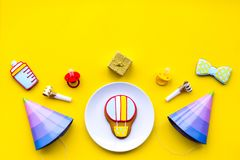 Celebrate child`s birthday. Cookies in shape of baby accesssories, party hats, gift box on yellow background top view.  stock photos
