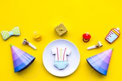 Celebrate child`s birthday. Cookies in shape of baby accesssories, party hats, gift box on yellow background top view.  stock image