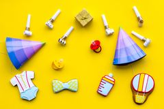Celebrate child`s birthday. Cookies in shape of baby accesssories, party hats, gift box on yellow background top view.  royalty free stock photography