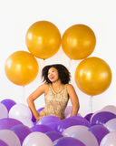 Celebrate good times! Attractive laughing young woman celebrates with balloons. Celebrate good times! Attractive laughing young woman surrounded by purple, gold royalty free stock photography