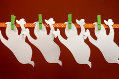 Celebrate Halloween with white ghost party bunting hanging from green pegs on a line Stock Image