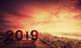 Celebrate 2019. Happy young businessman celebrate new year 2019 standing on rooftop of a skyscraper over big city sunset horizon background. Business research stock photography