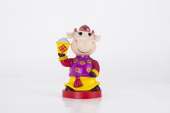 Celebrate the harvest cows doll. In the dress of Chinese dolls, hands holding a symbol of the agriculture, closed box full of food. Smiling face, festive royalty free stock photos
