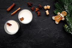 Celebrate new year winter evening with eggnog drink in glasses. ginger bread cookie, spruce branch and cinnamon . Black. Desk background top view. Mock up Stock Images