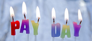 Celebrate: Pay Day. A macro image of colorful lighted candles spelling out pay day Royalty Free Stock Photo