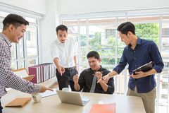 Celebrate success. Business team celebrate a good job in the office. Asian people. Business succes on mobile phone and computer. royalty free stock images
