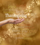 Celebrate Thanksgiving. Golden bokeh background with a string of glittery sparkles and a female hand outstretched with a white 'Thanksgiving' word floating above Royalty Free Stock Photos