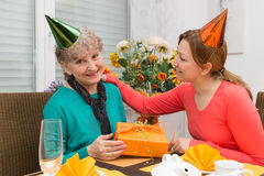 Celebrate together. Daughter giving her mother a present Royalty Free Stock Image