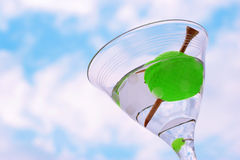 Celebrate the win. A golf ball olive with a tee toothpick in a martini against a blue sky with clouds (symbolic of the 19th hole in golf Royalty Free Stock Photo