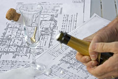 Celebrating. A closeup of a pair of hands holding an open bottle of champagne over some floor plans. A glass and the cork from the bottle have been placed on the Stock Image