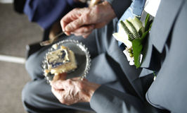 Celebrating a 60th wedding anniversary. Senior male with corsage on suit eating cake at 60th wedding anniversary . Focus on corsage Stock Photo