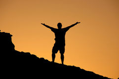 Celebrating an achievement. Man celebrating his accomplishment at the top of a mountain Stock Photos