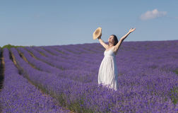Celebrating the beauty of life. Beautiful young woman wearing a white dress celebrating the beauty of life standing in the middle of a lavender field in bloom Stock Photos