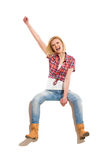 Celebrating blond woman sitting on a blank poster Royalty Free Stock Photography