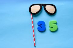 Flat lay top view number and sunglasses cute paper carnival mask. royalty free stock photos