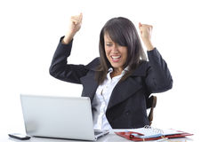 Celebrating businesswoman. Businesswoman at desk celebrating with hands in air and open laptop computer in foreground; white studio background Stock Image