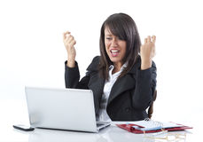 Celebrating businesswoman. Attractive young businesswoman celebrating at desk with laptop computer; white studio background Stock Photo