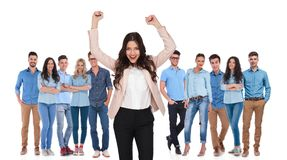 Celebrating businesswoman leader standing in front of her winner. Celebrating businesswoman team leader standing in front of her winner casual groupwith both stock image