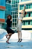 Celebrating Businesswomen. Two young businesswomen celebrating outside of an office building Royalty Free Stock Images