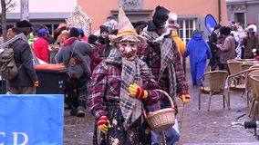 Celebrating Carnival in Konstanz (Germany). 02/04/2016. Carnival in different fancy dress in the old town. Two people in costume walking down the street of the stock video