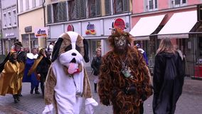 Celebrating Carnival in Konstanz (Germany). 02/04/2016. Carnival in different fancy dress in the old town. Two people in costume walking down the street of the stock video footage