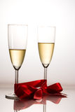 Celebrating with champagne. Celebrating having two fresh flute tied with a red ribbon filled with sparkling champagne Royalty Free Stock Images